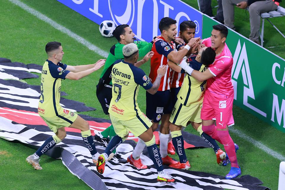 MEXICO CITY, MEXICO - SEPTEMBER 25: Jesus Molina #5 and Raul Gudino #1 of Chivas hold Henry Martin of America #21 to avoid a confrontation while Miguel Ponce #16 of Chivas puts a hand on Martin's face during the 10th round match between America and Chivas as part of the Torneo Grita Mexico A21 Liga MX at Azteca Stadium on September 25, 2021 in Mexico City, Mexico. (Photo by Hector Vivas/Getty Images)