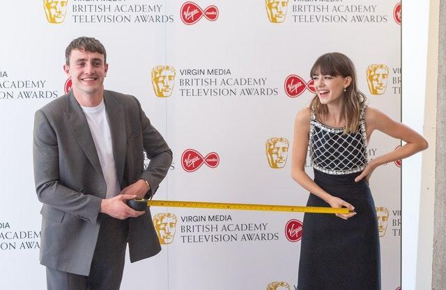 Paul Mescal and Daisy Edgar-Jones measure out one metre of safe social distance as they pose for photographers at the Virgin Media Bafta TV awards at the TV Centre, Wood Lane, London