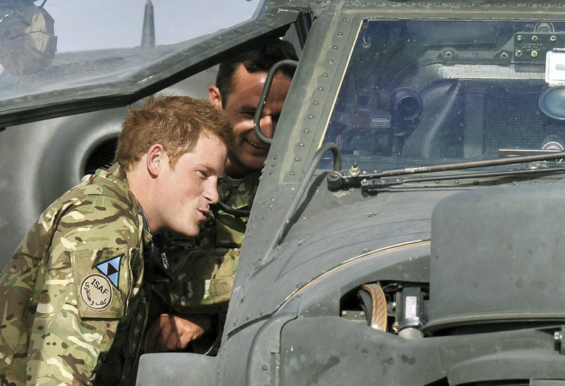 In this Friday, Sept. 7, 2012 photo made available on Sunday, Sept. 9, 2012, Britain's Prince Harry examines the cockpit of an Apache attack helicopter with an unidentified member of his squadron, at Camp Bastion in Afghanistan, where he starts his tour of duty as a co-pilot gunner. The 27-year-old Army captain Prince Harry, known as Captain Harry Wales, is on his second tour of duty in Afghanistan but will go through the usual familiarization process before becoming operational and flying attack helicopters. (AP Photo / John Stillwell, Pool)
