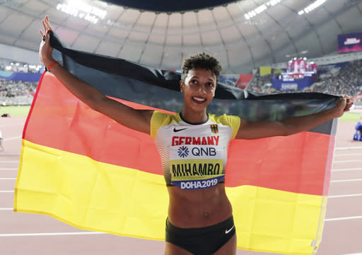FILE - In this Sunday, Oct. 6, 2019 file photo, Malaika Mihambo, of Germany, celebrates her gold medal in the women's long jump final at the World Athletics Championships in Doha, Qatar. World long jump champion Mihambo wants to double up with the 100 meters at the Tokyo Olympics next summer. That's definitely the plan for next year. I've noticed that I really like sprinting, Mihambo told German news magazine Der Spiegel in an interview published Saturday, Nov. 21, 2020 but said it would be tough to establish herself as a sprinter. (AP Photo/Hassan Ammar, file)