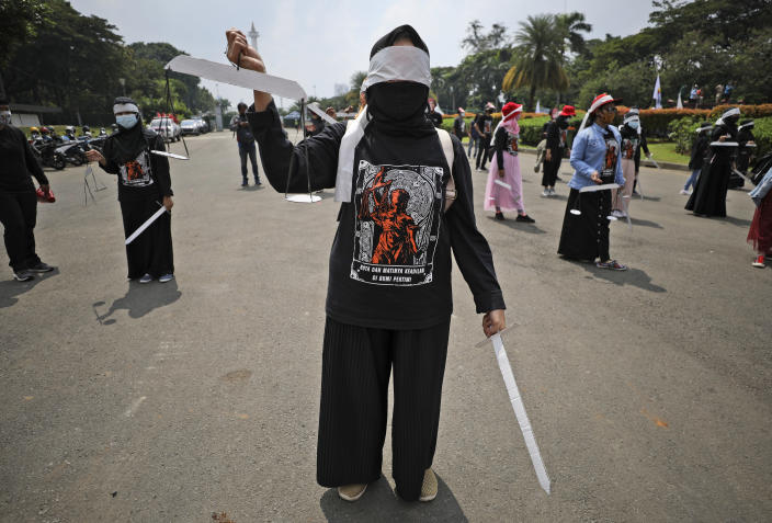 Indonesian workers stand spaced apart as a precaution against coronavirus outbreak, while holding mock sword and scales to symbolize justice during a May Day rally in Jakarta, Indonesia, Saturday, May 1, 2021. Workers in Indonesia marked international labor day on Saturday curtailed by strict limits on public gatherings to express anger at a new law they say could harm labor rights and welfare. (AP Photo/Dita Alangkara)