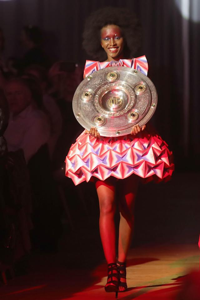 A model presents the Bundesliga trophy during a party of Bayern Munich at the Nockherberg beer garden in Munich, Germany, May 12, 2018. Picture taken May 12, 2018. Alexander Hassenstein/Pool via Reuters