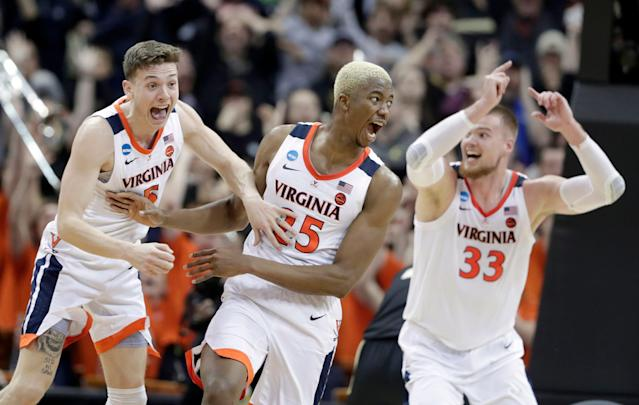 Virginia's Mamadi Diakite, center, reacts with teammates Kyle Guy and Jack Salt after hitting a shot to send the Cavaliers' Elite Eight game against Purdue to overtime. (AP)