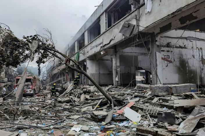 Workers search for victims in a building damaged by a gas line explosion which left at least 12 people dead and nearly 140 others injured in Shiyan, in central China's Hubei province
