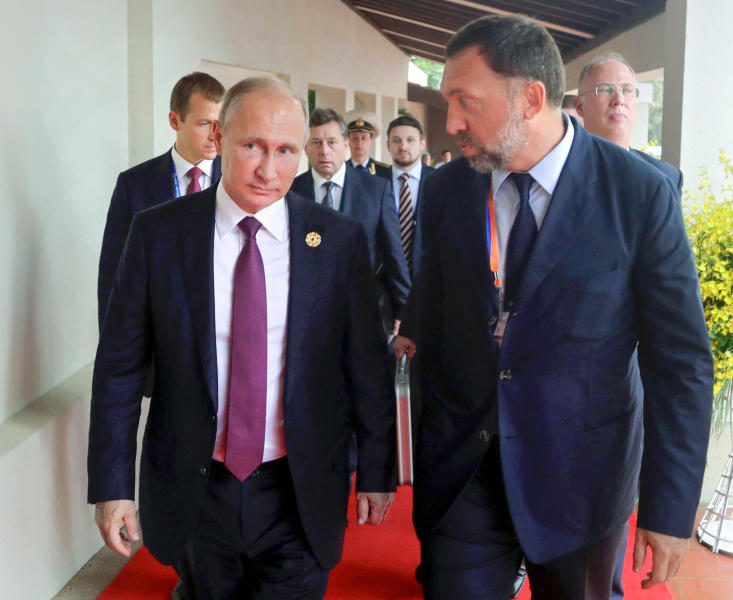 FILE - This Nov. 10, 2017, file photo shows Russia's President Vladimir Putin, left, and Russian metals magnate Oleg Deripaska, right, walking to attend the APEC Business Advisory Council dialogue in Danang, Vietnam. (Mikhail Klimentyev, Sputnik, Kremlin Pool Photo via AP, File)
