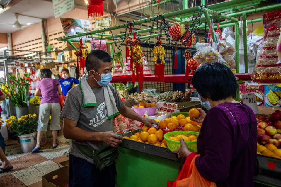 Fruit stall owner Tan Boon Siong seen here arranging oranges on display at his stall at the Yulek Morning Market. — Picture by Shafwan Zaidon