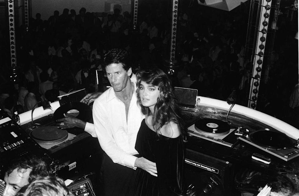 <p>Calvin Klein and Brooke Shields stand in the DJ booth at Studio 54 nightclub, New York City.</p>