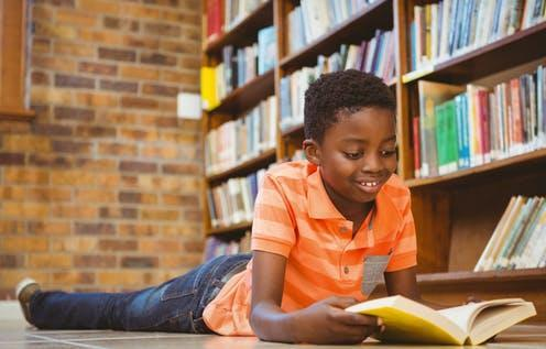 """<span class=""""caption"""">It is important that children sees themselves in the books that read. </span> <span class=""""attribution""""><a class=""""link rapid-noclick-resp"""" href=""""https://www.shutterstock.com/image-photo/cute-little-boy-reading-book-library-258035060"""" rel=""""nofollow noopener"""" target=""""_blank"""" data-ylk=""""slk:wavebreakmedia/Shutterstock"""">wavebreakmedia/Shutterstock</a></span>"""