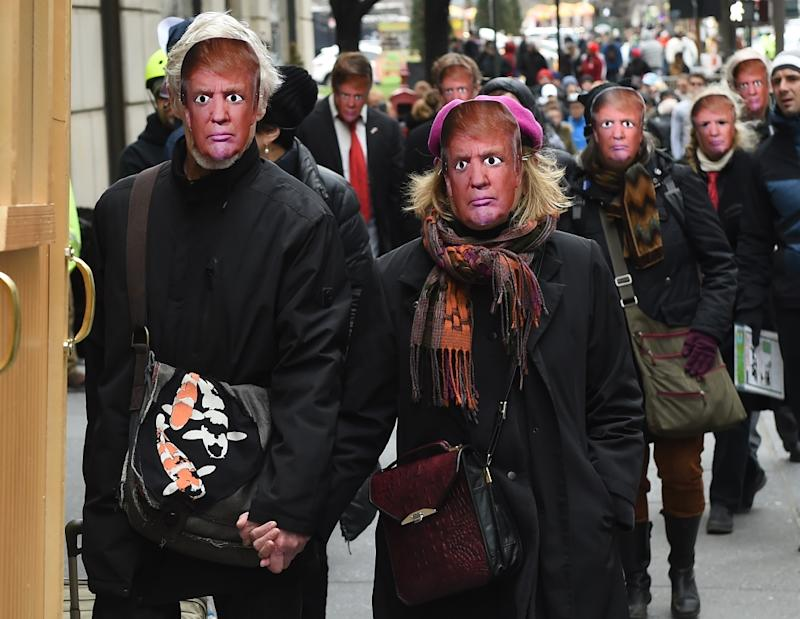 People wearing masks of US President Donald Trump take part in the 32nd Annual April Fools' Day Parade in New York on April 1, 2017