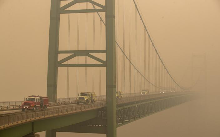 """Fire trucks drive over the Bidwell Bar Bridge in thick smoke from the Bear fire on Thursday, Sept. 10, 2020, in Oroville, Calif. <span class=""""copyright"""">(Brian van der Brug / Los Angeles Times)</span>"""