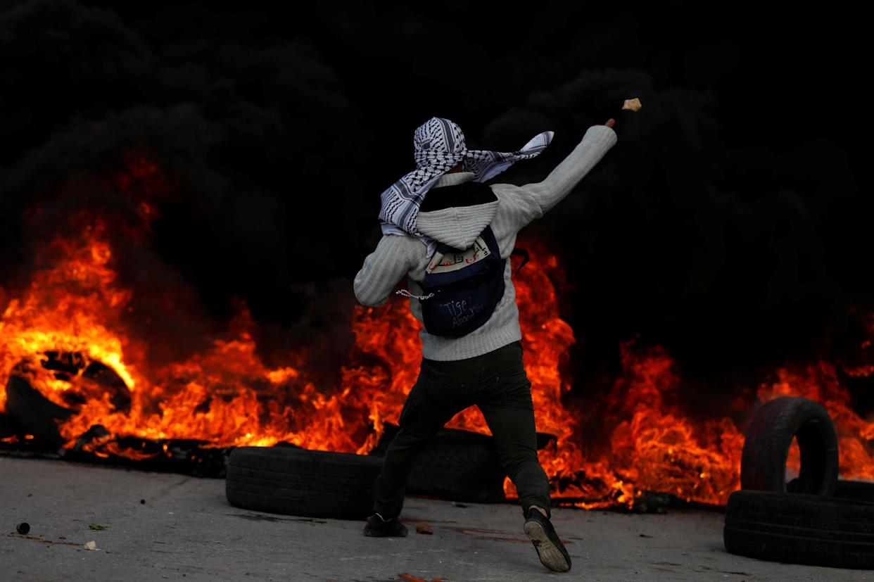A Palestinian protester hurls stones towards Israeli troops during clashes near the Jewish settlement of Beit El, near the West Bank city of Ramallah December 7, 2017.