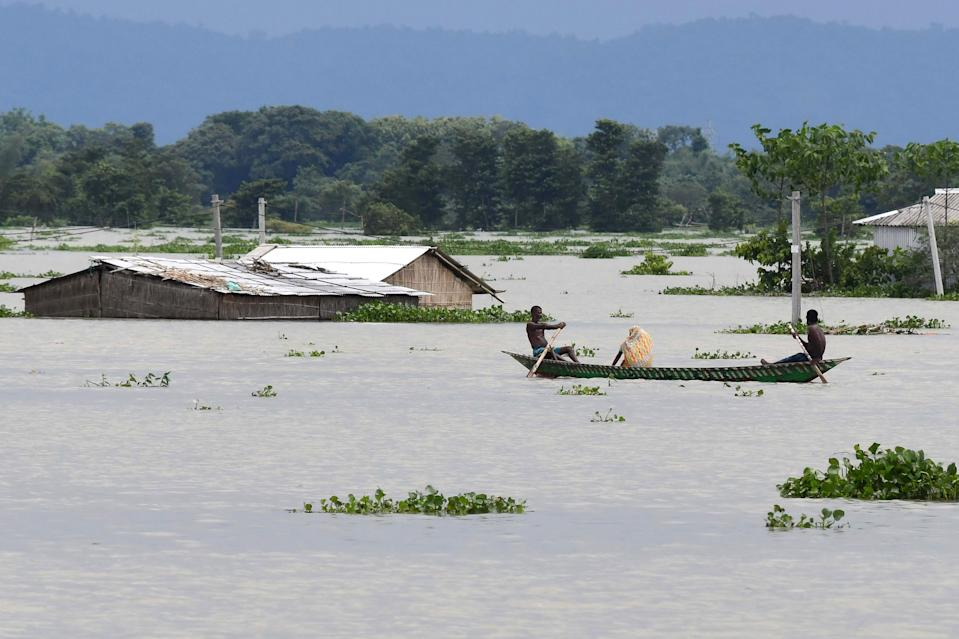 Villagers travel on a boat at the flood affected area of Gagalmari village in Morigaon district of Assam state on July 14, 2020. (Photo by BIJU BORO/AFP via Getty Images)