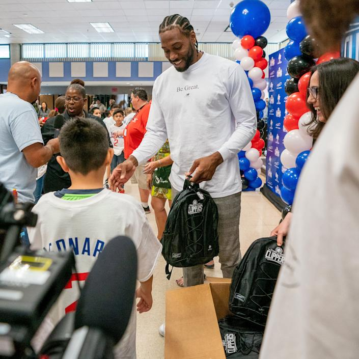 Kawhi Leonard hands out backpacks to students on Tuesday.  (Photo: Colette Garcia (L.A. Clippers))
