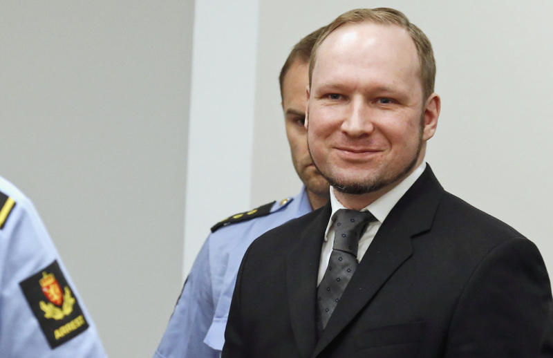 """Confessed mass killer Anders Behring Breivik smiles as he arrives in the courtroom, Friday, Aug. 24, 2012, in Oslo, Norway. A Norwegian court sentenced Anders Behring Breivik to prison on Friday, denying prosecutors the insanity ruling they hoped would show that his massacre of 77 people was the work of a madman, not part of an anti-Muslim crusade. Reading the ruling, Judge Wenche Elisabeth Arntzen handed down a sentence of """"preventive detention"""" of at least 10 years and a maximum of 21 years. (AP Photo/Heiko Junge/NTB scanpix, Pool)"""