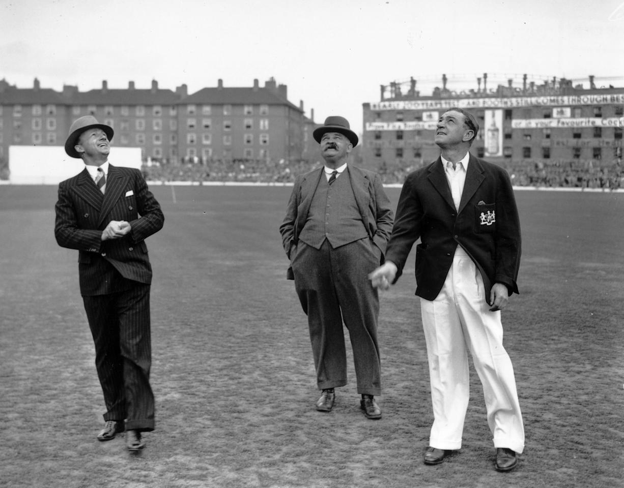 August 1938:  Don Bradman (left, 1908 - 2001) of Australia and English cricketer Wally Hammond (1903 - 1965) watching the 'toss-up' before a test match at the Oval. 'Bosser' Martin, the legendary groundsman, looks on.  (Photo by Central Press/Getty Images)