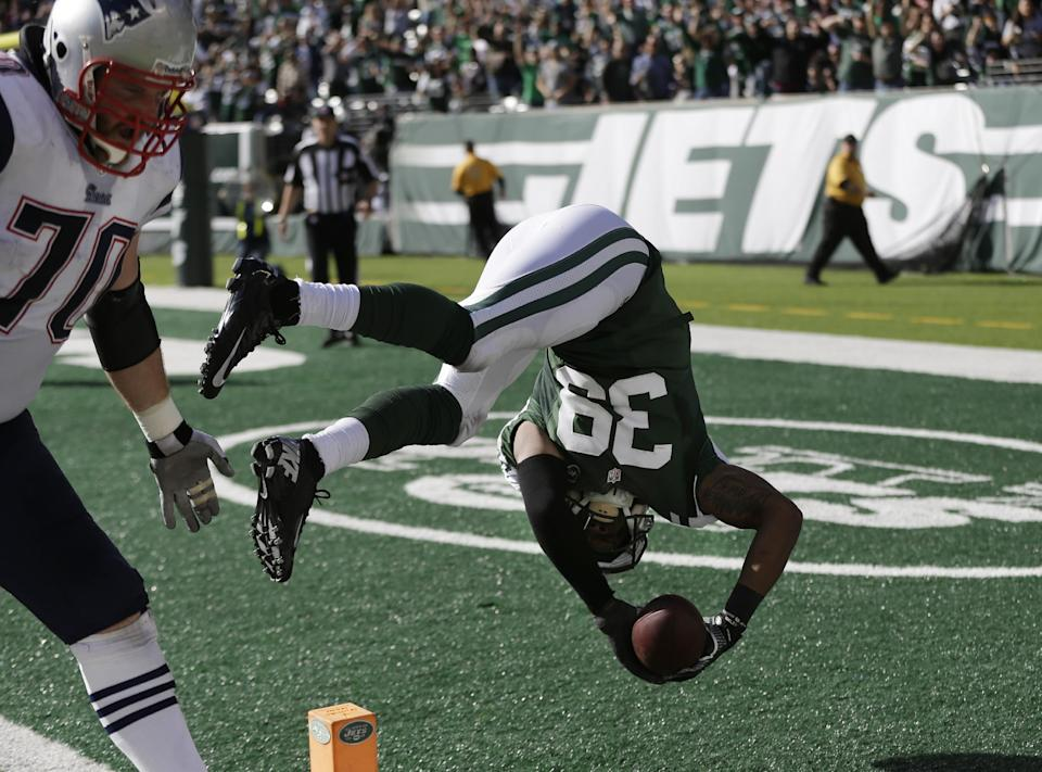 New York Jets free safety Antonio Allen (39) flips into the end zone for a touchdown after intercepting a pass by New England Patriots' Tom Brady during the second half of an NFL football game Sunday, Oct. 20, 2013, in East Rutherford, N.J. New England Patriots' Logan Mankins (70) trails the play. (AP Photo/Seth Wenig)