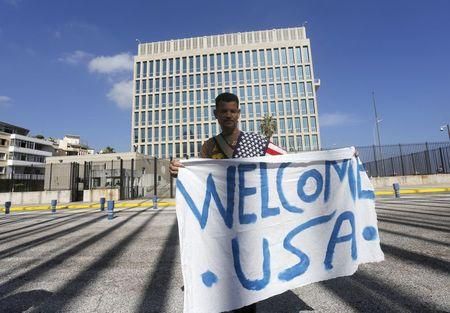A man hold a banner in front of the U.S. Interests Section in Havana July 20, 2015.   REUTERS/Stringer