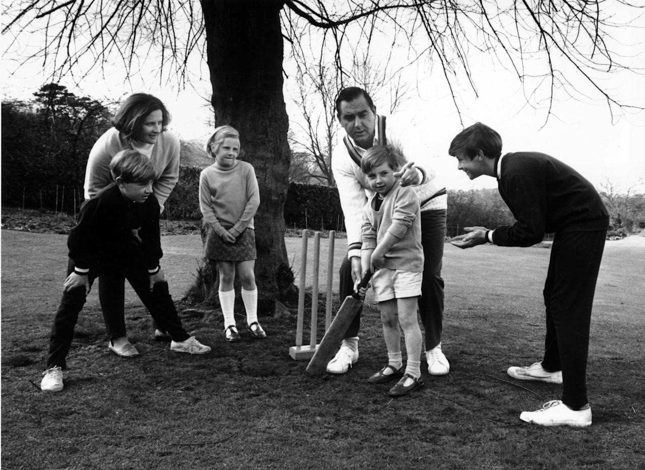 April 1970:  Cricketer Colin Cowdrey (1932 - 2000) teaching his children how to play cricket on the lawn of the family home in Surrey.  (Photo by Chris Ware/Keystone Features/Getty Images)