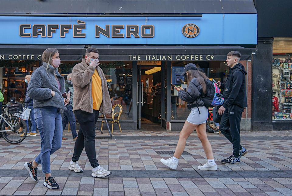 Shoppers wearing face masks walk past Cafe Nero coffee shop. (Photo by Michael McNerney / SOPA Images/Sipa USA)