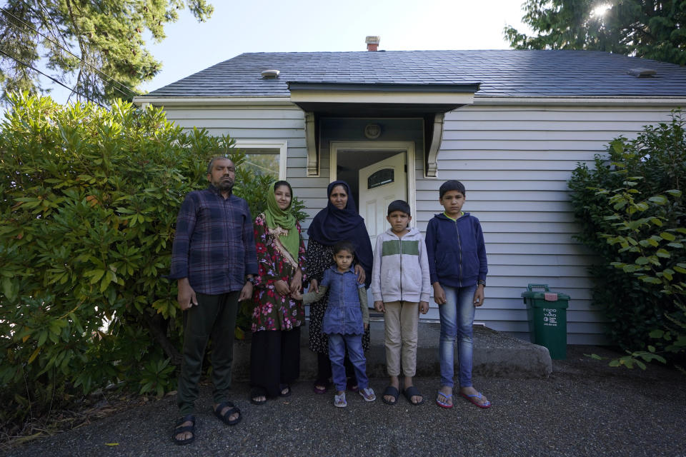 Abdul, left, who worked as a mechanic before he left Kabul, Afghanistan with his family about a month ago, poses for a photo, Thursday, Sept. 16, 2021, with his family in front of a rental house where they have been provided a place to stay in Seattle. The home is owned by Thuy Do, who was nine years old when her family arrived in the United States from Vietnam in the 1980s. Now Do and her husband have offered their vacant rental home to refugee resettlement groups to house newly arriving Afghans in need of a place to stay. (AP Photo/Ted S. Warren)