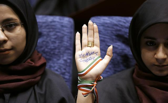 <p>A supporter of Iranian conservative presidential candidate and Tehran mayor Mohammad Bagher Ghalibaf, holds up her hand, wrapped with a ribbon in the colors of the Iranian flag, as she attends a campaign rally in Tehran, Iran, May 14, 2017 (Photo: Atta Kenare/AFP/Getty Images) </p>