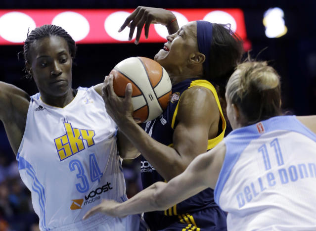 Indiana Fever forward Tamika Catchings, center, drives to the basket between Chicago Sky center Sylvia Fowles, left, and forward Elena Delle Donne during the first half in Game 1 of the WNBA basketball Eastern Conference semifinal series on Friday, Sept. 20, 2013, in Rosemont, Ill. (AP Photo/Nam Y. Huh)