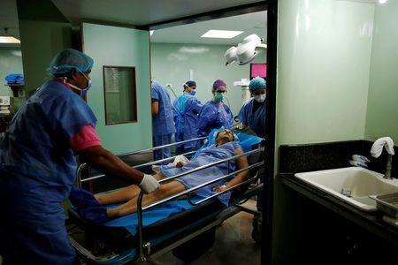 Medical personnel move a woman after her sterilization surgery in the operating room of a hospital in Caracas, Venezuela July 27, 2016. REUTERS/Carlos Garcia Rawlins