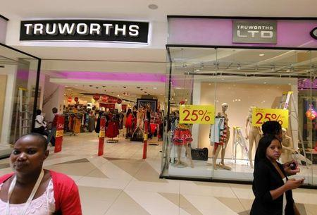 Shoppers walk past a Truworths shop with Sale advertisements on its windows at the Sandton shopping mall in Johannesburg