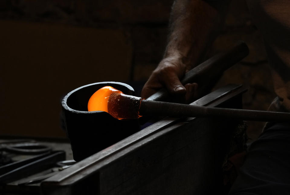 A glass-worker models heated glass in a factory in Murano island, Venice, Italy, Thursday, Oct. 7, 2021. The glassblowers of Murano have survived plagues and pandemics and have transitioned to highly prized artistic creations to outrun competition from Asia, but surging energy prices may be their doom. (AP Photo/Antonio Calanni)