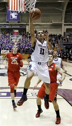Northwestern guard Reggie Hearn (11) shoots past Maryland center Alex Len (25) and guard Logan Aronhalt during the first half of an NCAA college basketball game, Tuesday, Nov. 27, 2012, in Evanston, Ill. (AP Photo/Charles Rex Arbogast)