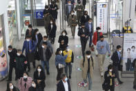 An employee, center right, wearing a face mask and face shield to help protect against the spread of the coronavirus, guides a passenger at the Seoul Railway Station in Seoul, South Korea, Thursday, Oct. 22, 2020. (AP Photo/Ahn Young-joon)