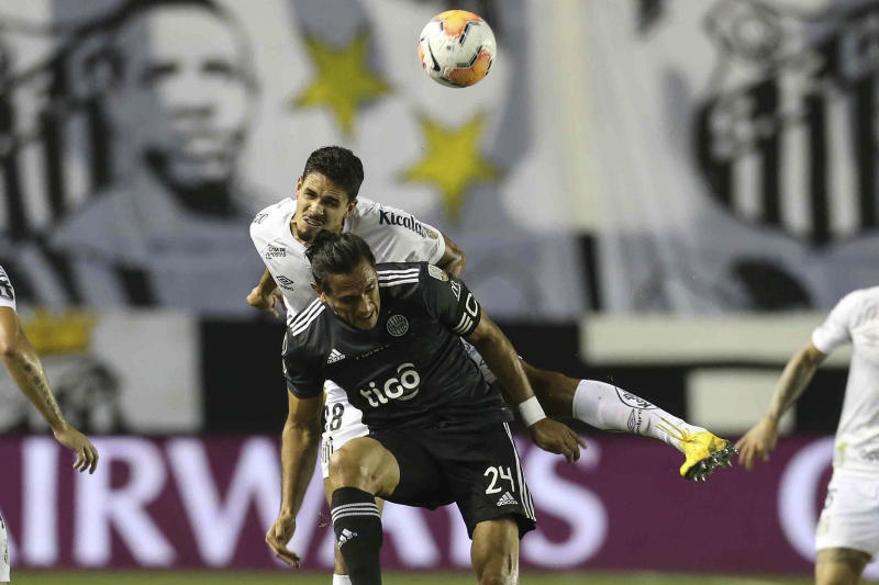 Brazil's Santos defender Lucas Verissimo (L) and Paraguay's Olimpia forward Roque Santa Cruz vie for the ball during their closed-door Copa Libertadores group phase football match at the Vila Belmiro stadium in Santos, Brazil, on September 15, 2020, amid the COVID-19 novel coronavirus pandemic. (Photo by GUILHERME DIONIZIO / POOL / AFP) (Photo by GUILHERME DIONIZIO/POOL/AFP via Getty Images)