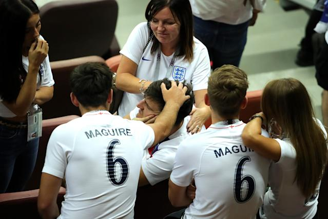 Family time: Harry Maguire is comforted by his mum and brothers at the Luzhniki Stadium