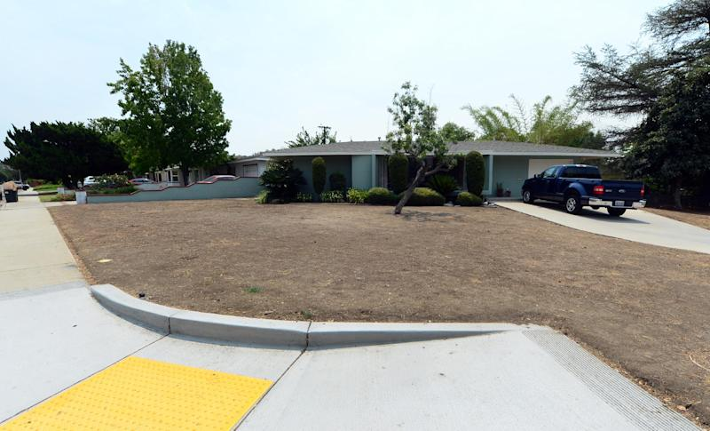 A resident's brown lawn can be seen in the city of Glendora, east of Los Angeles on July 29, 2014 in California, where a neighbor made headlines after receiving a letter from the city threatening fines if they didn't water their lawn