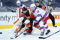 Philadelphia Flyers' Erik Gustafsson (56) and New York Rangers' Alexis Lafreniere (13) battle for the puck during the second period of an NHL hockey game, Wednesday, Feb. 24, 2021, in Philadelphia. (AP Photo/Matt Slocum)