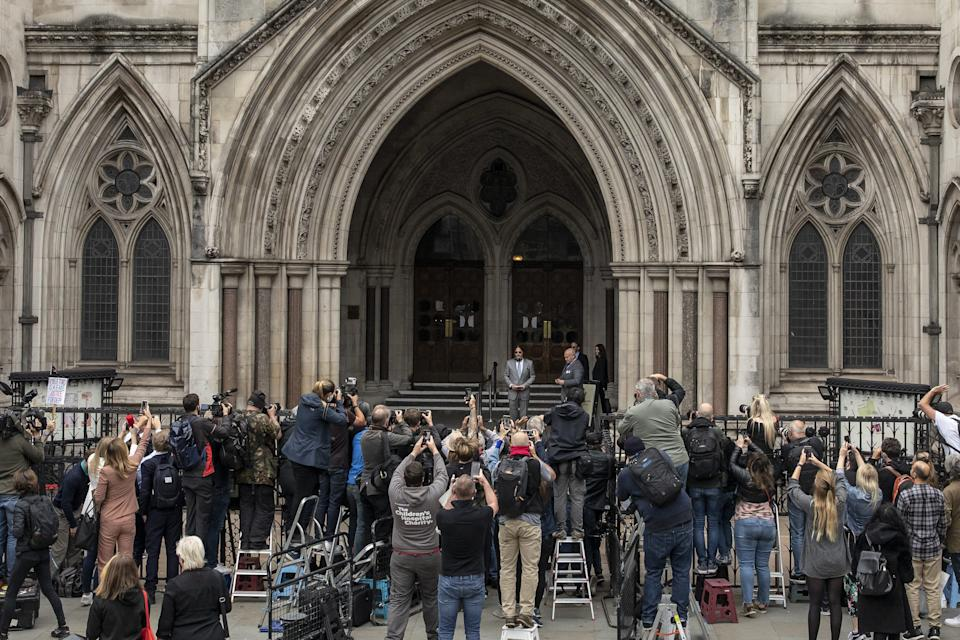 A crowd of fans and media photographers greet Johnny Depp as he arrives for court in London on July 16, 2020.