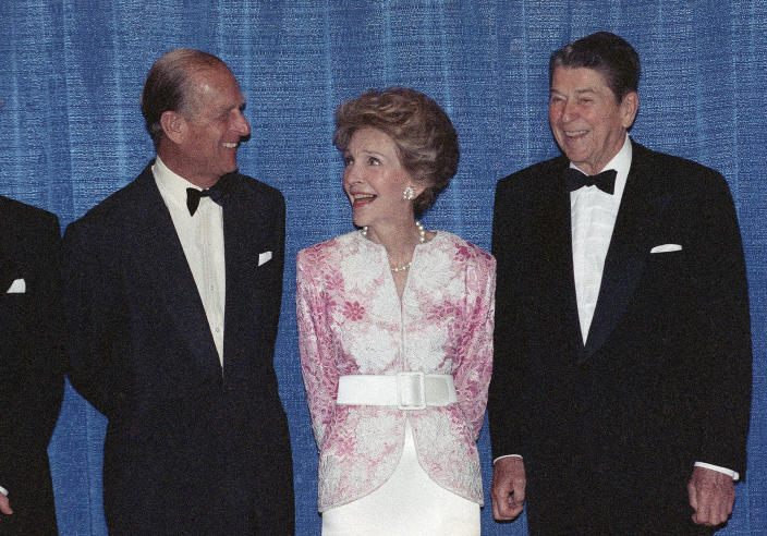 FILE - In this Wednesday, May 17, 1989 file photo, Britain's Prince Philip talks with former US President Ronald Reagan, right, and his wife Nancy Reagan prior to a dinner in Beverly Hills, Calif. The Prince presented the Winston Churchill Award to the former president. Buckingham Palace says Prince Philip, husband of Queen Elizabeth II, has died aged 99. (AP Photo/Doug Pizac, File)