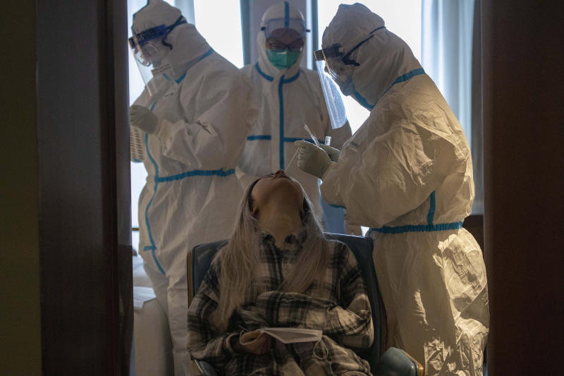 A woman takes a COVID-19 test at a quarantine hotel in Wuhan in central China's Hubei province on Tuesday, March 31, 2020. China on Tuesday reported just one new death from the coronavirus and a few dozen new cases, claiming that all new cases came from overseas. (AP Photo/Ng Han Guan)