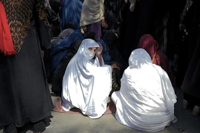 Women wait in front of a bank to withdraw money in Kabul (AFP/BULENT KILIC)