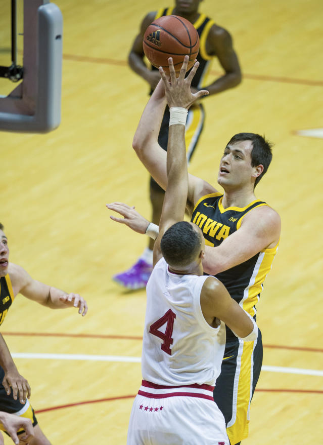 Iowa forward Ryan Kriener (15) shoots over the defense of Indiana forward Trayce Jackson-Davis (4) during the second half of an NCAA college basketball game, Thursday, Feb. 13, 2020, in Bloomington, Ind. (AP Photo/Doug McSchooler)