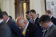 Texas State Rep. Andrew Murr, R-Kerrville, center, and fellow lawmakers pray as they prepare to debate voting bill SB1 in the House Chamber at the Texas Capitol, Thursday, Aug. 26, 2021, in Austin, Texas. (AP Photo/Eric Gay)