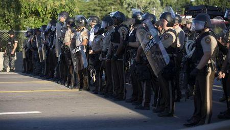 Police officers keep watch while demonstrators protest the death of black teenager Michael Brown in Ferguson