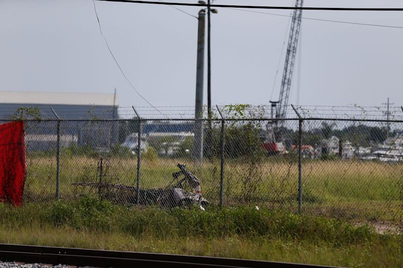The charred wreckage of a private plane is seen in a field near the Industrial Canal and New Orleans Lakefront airport, in New Orleans, Friday, Aug. 16, 2019.