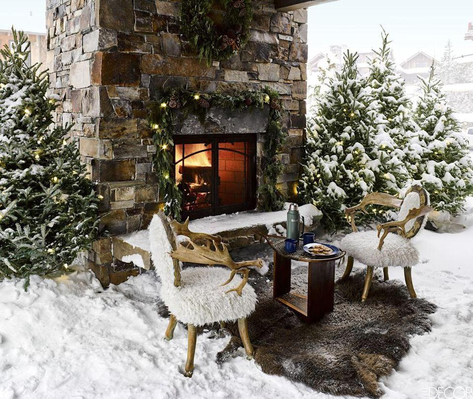 <p>A pair of sheepskin-covered moose-antler chairs surround an outdoor fireplace lush with pine. </p>