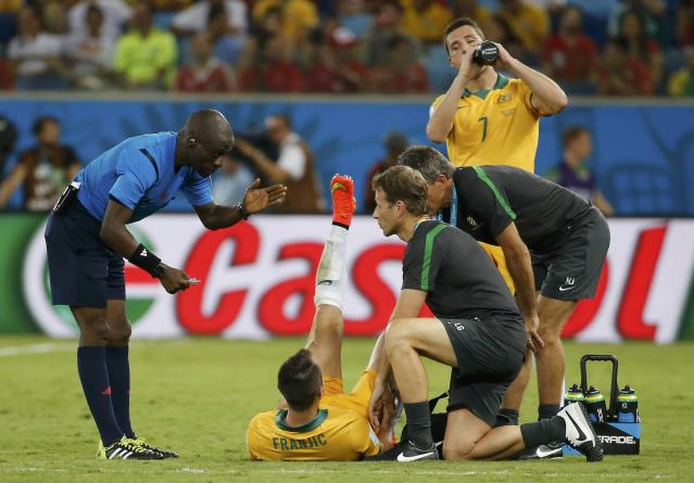 Referee Noumandiez Doue of Ivory Coast (L) gestures near Australia's Ivan Franjic (bottom C) as he lies on the pitch during the team's 2014 World Cup Group B soccer match against Chile at the Pantanal arena in Cuiaba June 13, 2014. REUTERS/Eric Gaillard (BRAZIL - Tags: SOCCER SPORT WORLD CUP)