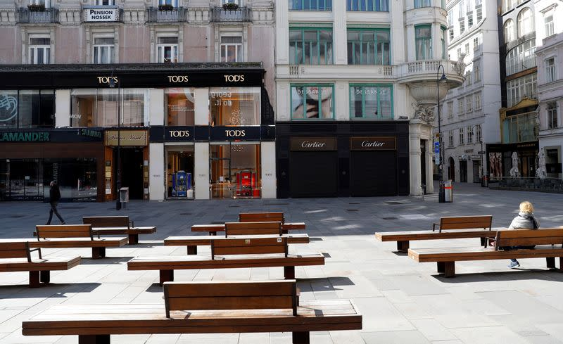 A person sits next to closed shops in Vienna