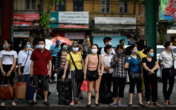 People wearing protective face masks wait at a bus stop as they return from work in Hanoi on July 29, 2020. (Photo by Manan VATSYAYANA / AFP) (Photo by MANAN VATSYAYA - AFP