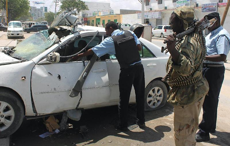 Somali security forces look at the debris after a car bomb explods, killing one person and injuring several others in the capital Mogadishu on October 25, 2014