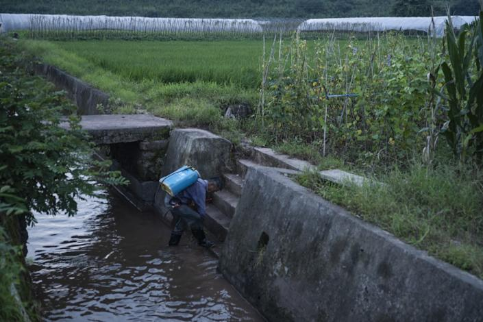 """A farmer in Xixinan village steps into a stream encased in concrete. China's approach to its water system focuses on speeding water through artificial walls, says Peking University professor Yu Kongjian. <span class=""""copyright"""">(Liu Bowen / For the Times)</span>"""