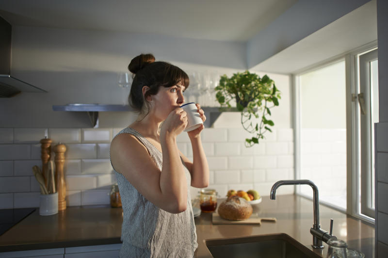 Woman drinking from mug in zero waste kitchen.